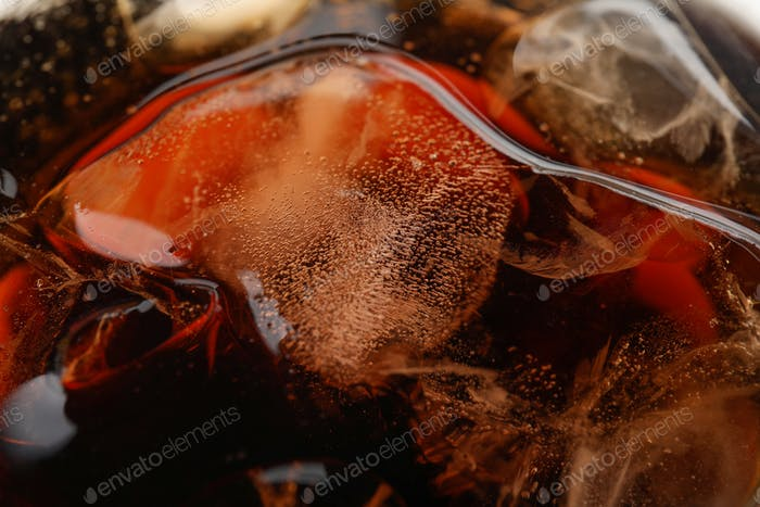 Soda drink with ice, close up and selective focus