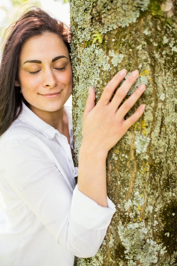 Beautiful brunette hugging a tree on a sunny day