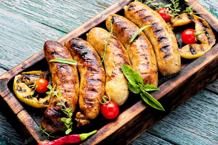 Grilled sausages on cutting board