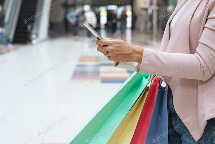 Shopping App. Black Woman Carrying Shopper Bags And Using Smartphone In Mall