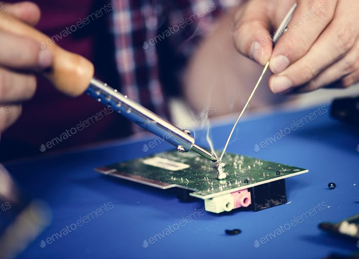 Closeup of hands soldering tin to electronics circuit board