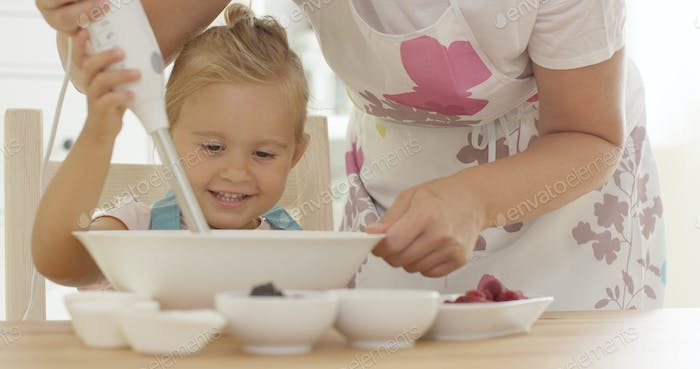 Cute happy little girl helping with the baking