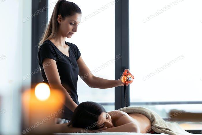 Frau mit heißem Wachs von einer Kerze für Rückenmassage, um eine hübsche Frau auf dem Spa-Center.