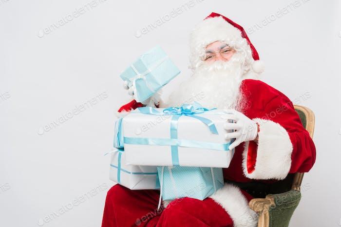 Foto von glücklichem Weihnachtsmann mit Geschenkboxen, die sie betrachten
