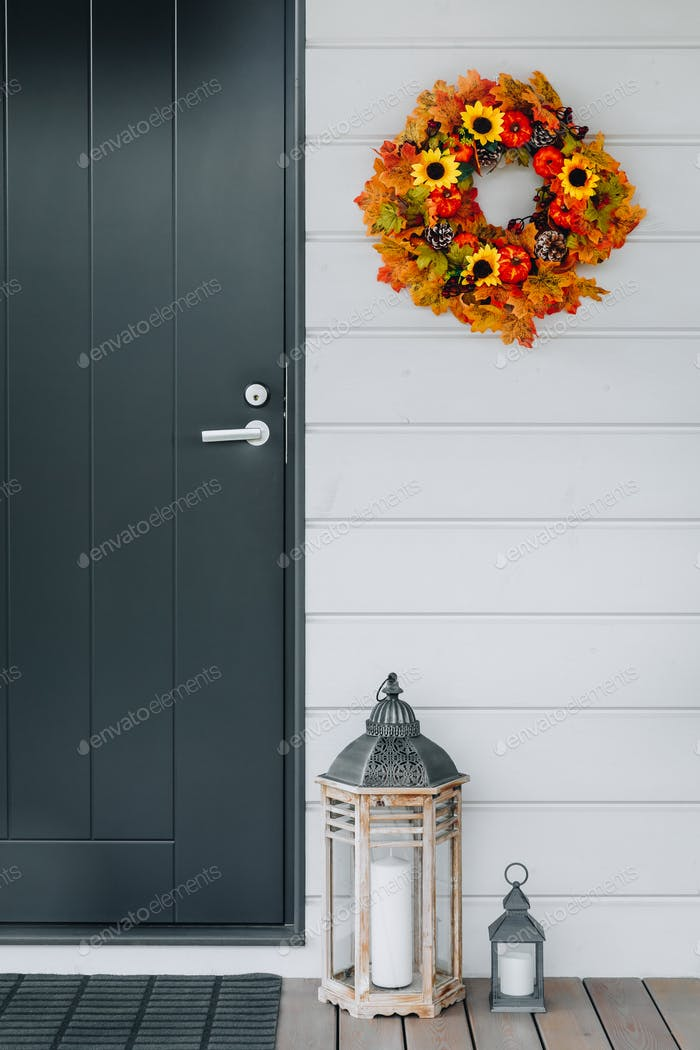 Autumn wreath with sunflowers, pumpkins and maple leaves on front door