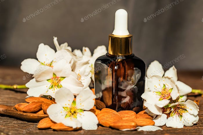 Almonds, oil and white flowers on grey background