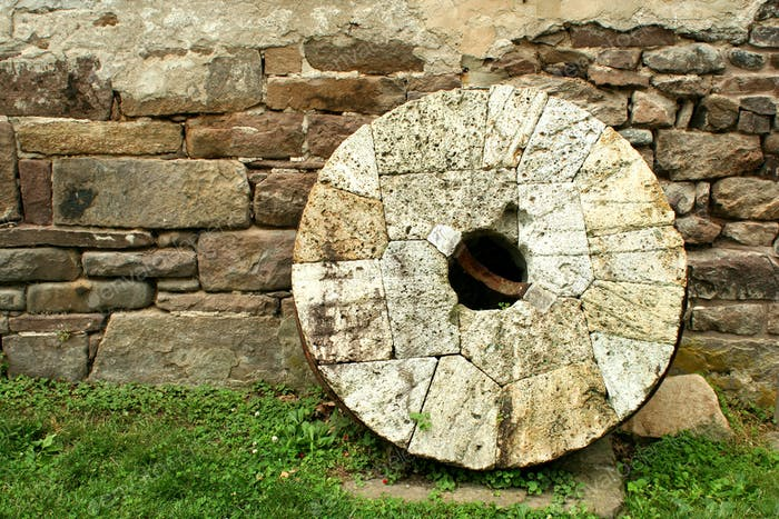 Old millstone leaning on a wall