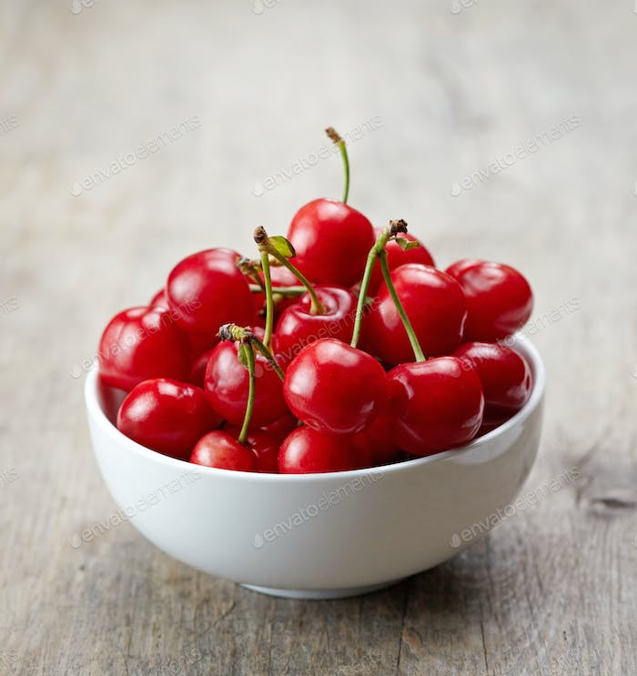 fresh red cherries in white bowl