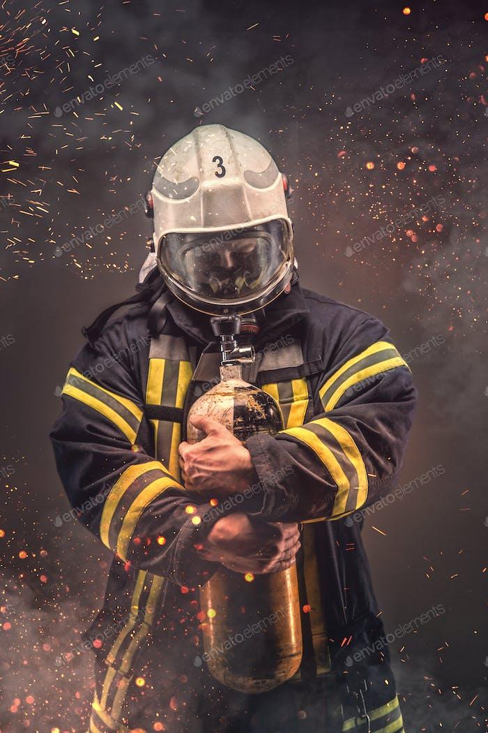 Firefighter in helmet and mask holds oxygen tanks.