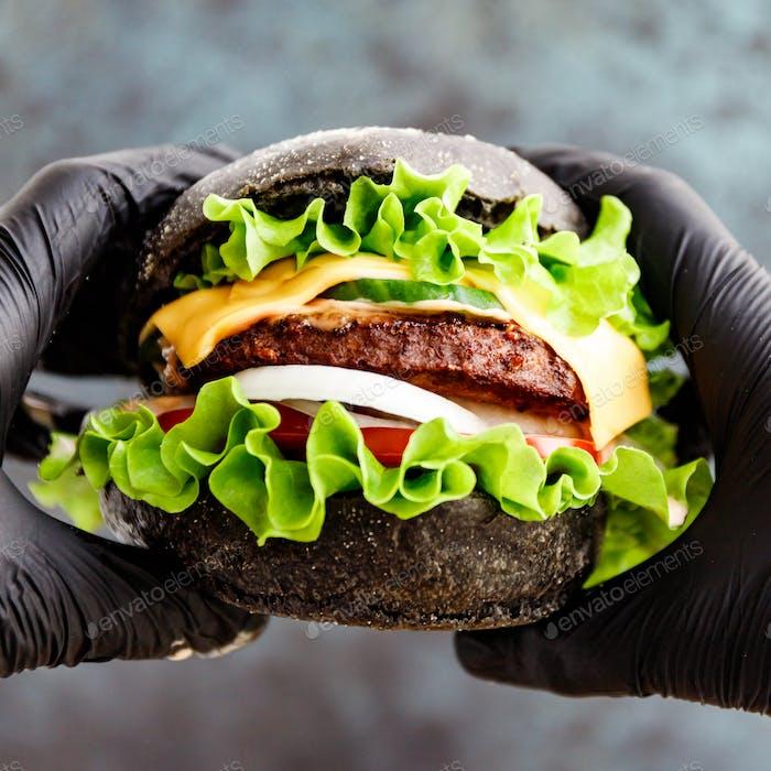 Hands in black gloves hold a big black burger
