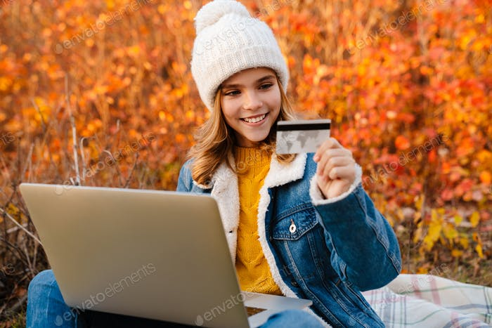 Girl in park using laptop computer while holding credit card
