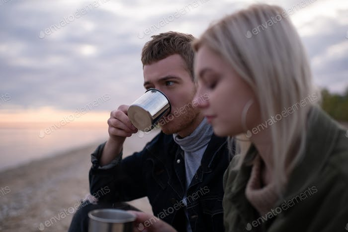 Man drinking tea near girlfriend in countryside
