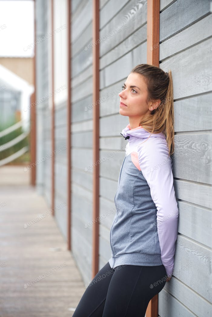 Sullen looking sporty woman leaning against wall outside