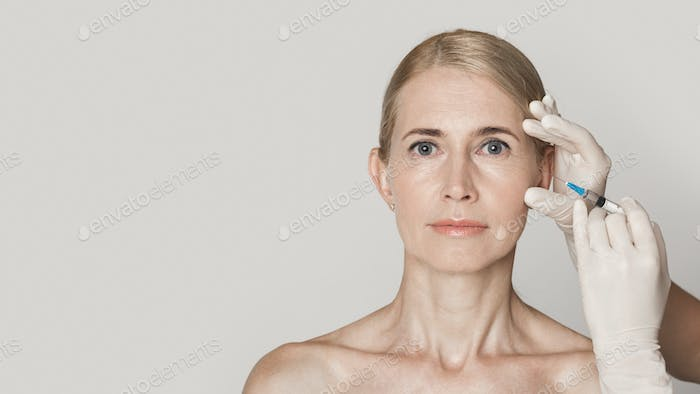 Middle aged woman getting anti aging injection