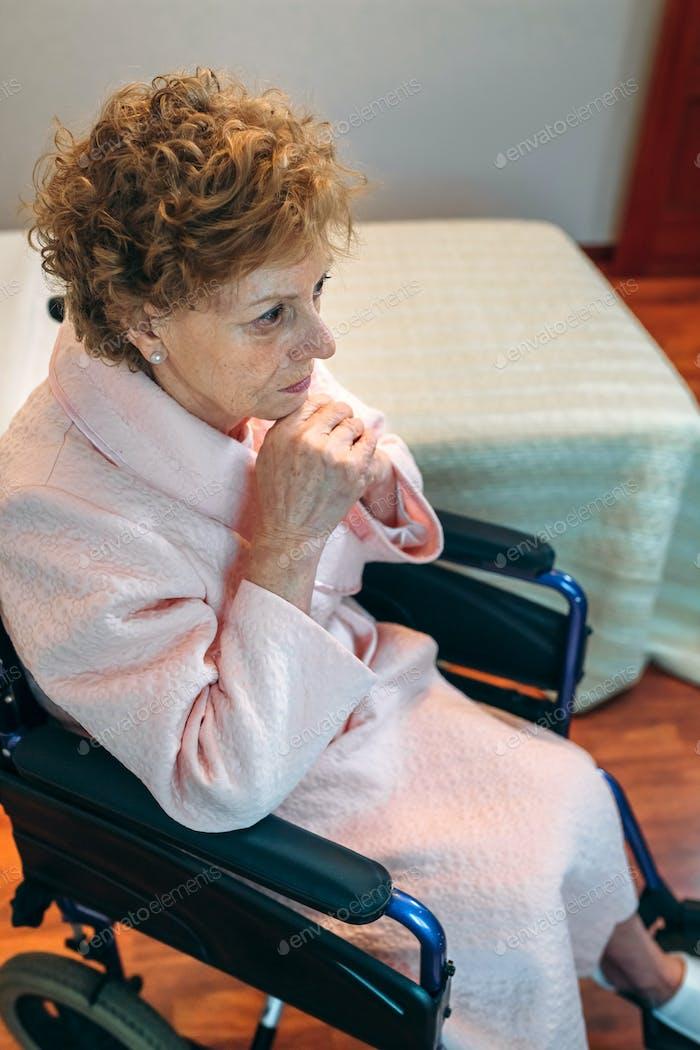 Senior woman in a wheelchair alone