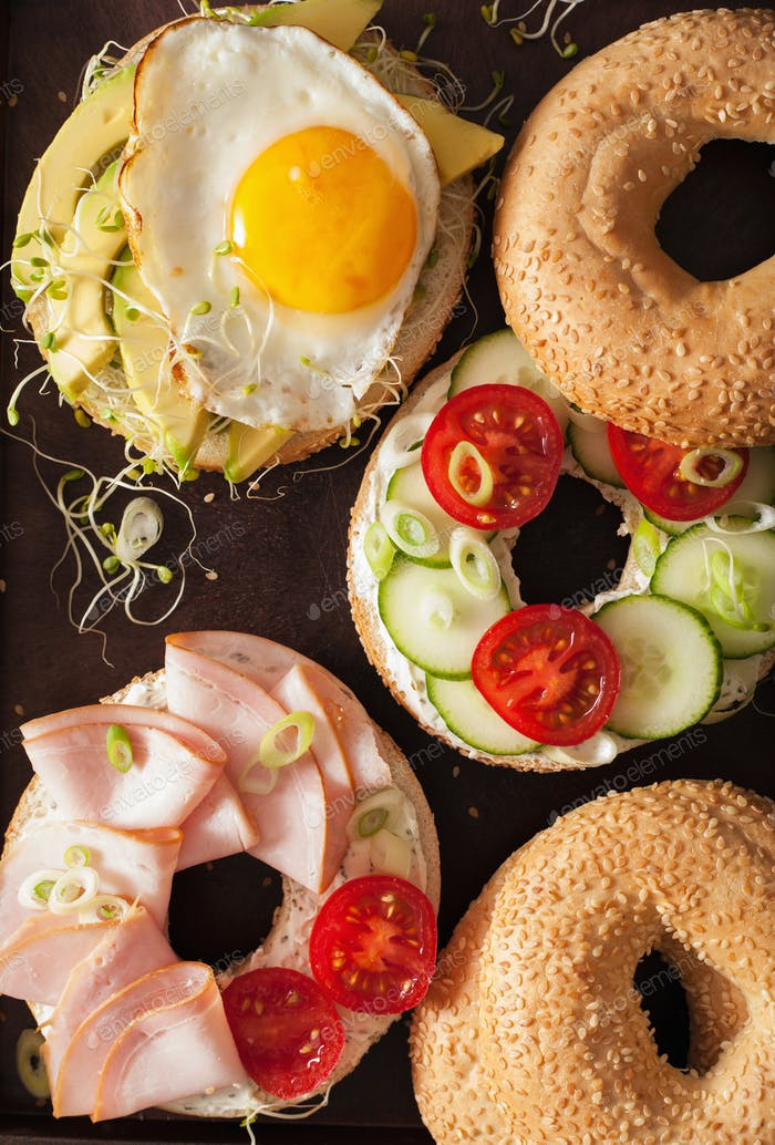 variety of sandwiches on bagels: egg, avocado, ham, tomato, soft