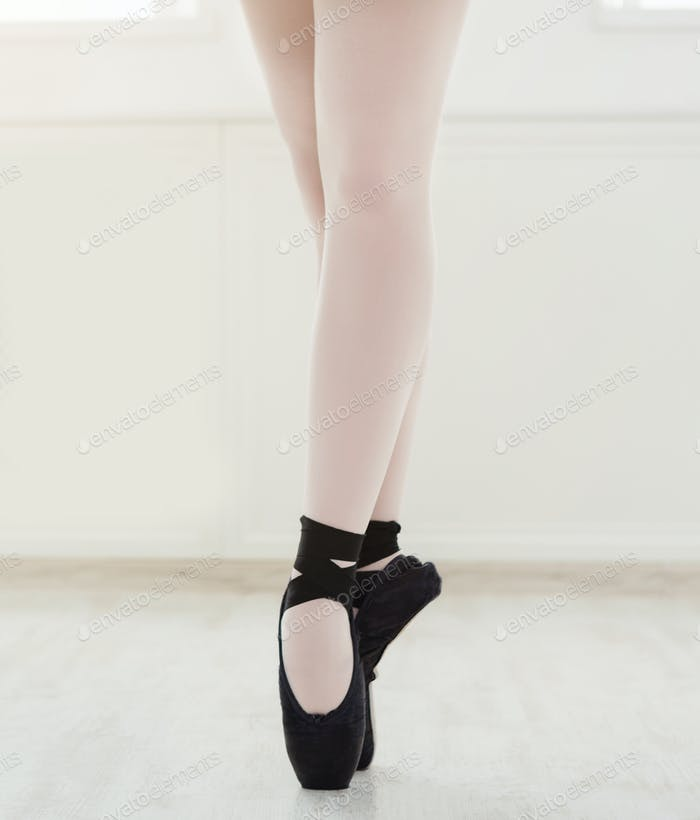 Ballerina in pointe shoes, graceful legs, ballet background