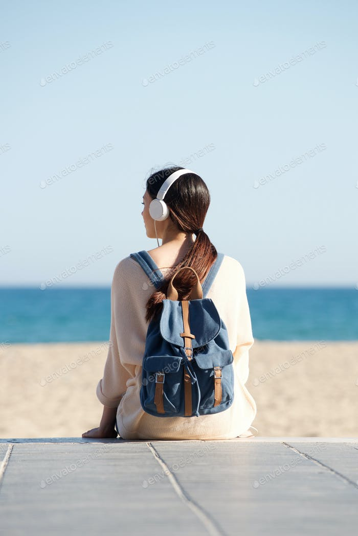 Woman sitting by sea with headphones and backpack