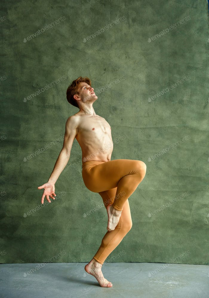 Ballet dancer poses at grunge wall, dancing studio