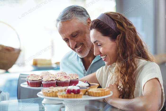 Happy couple looking at pastries in the bakery story