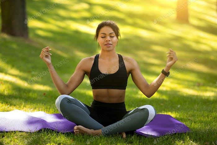 Peaceful black girl in sportswear meditating at park