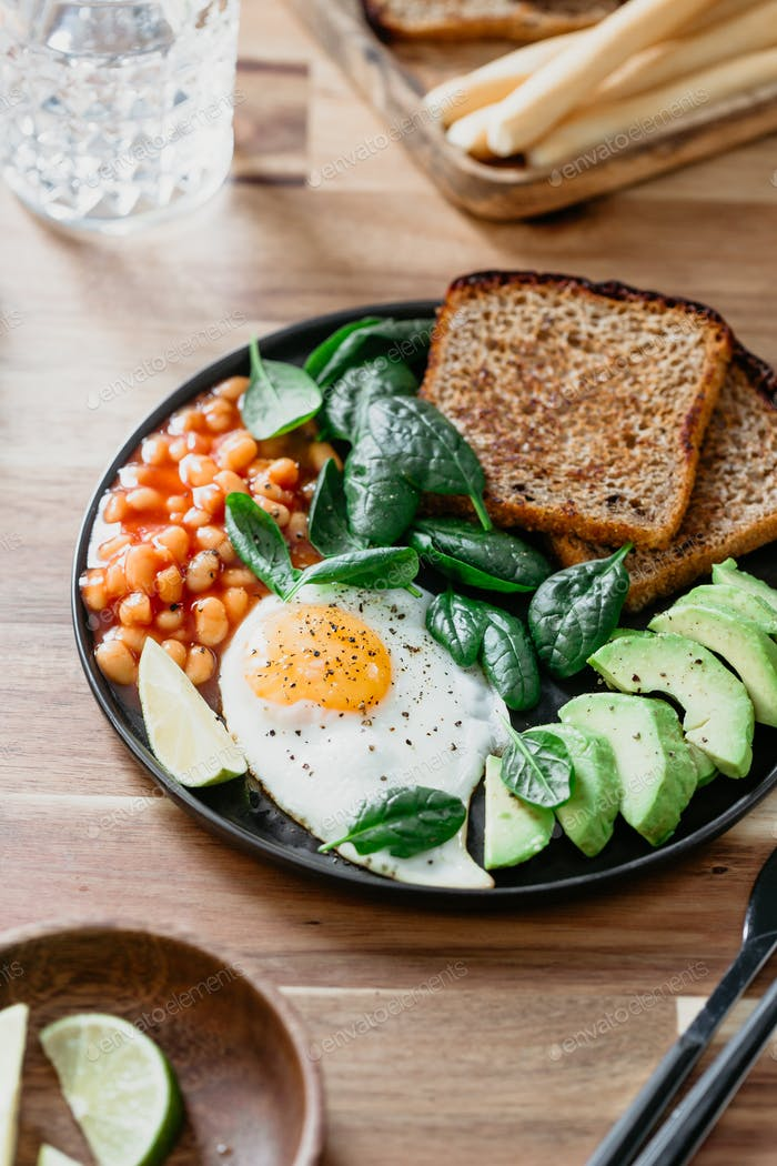 Fried egg, avocado, toasts, beans and fresh spinach. Healthy eating concept.