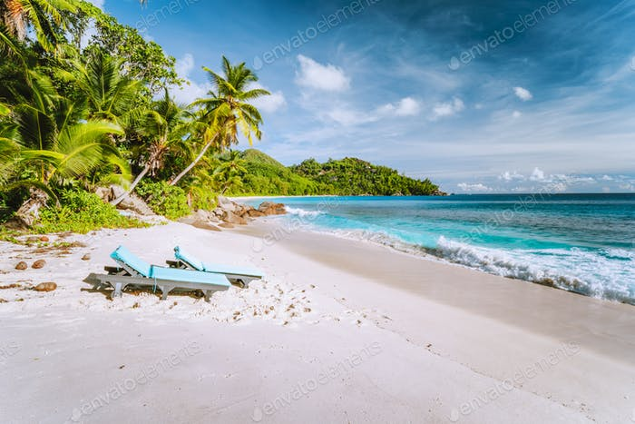Mahe, Seychelles. Sun lounger at beautiful Anse intendance, tropical beach. Blue ocean waves, sandy
