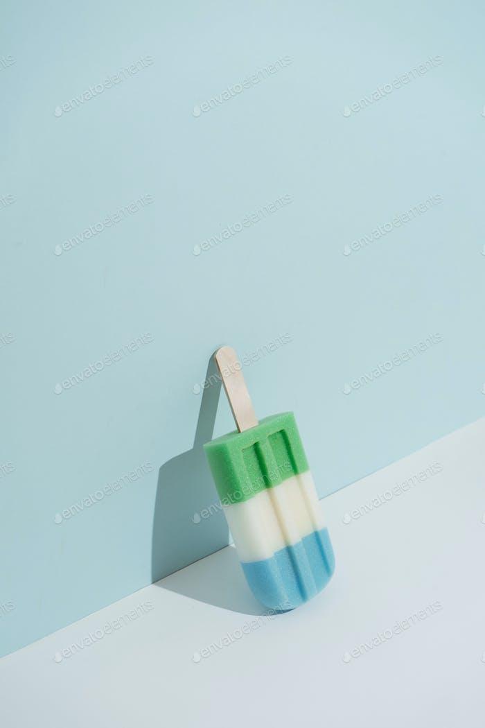 Icecream popsicle on blue background. Minimal style.