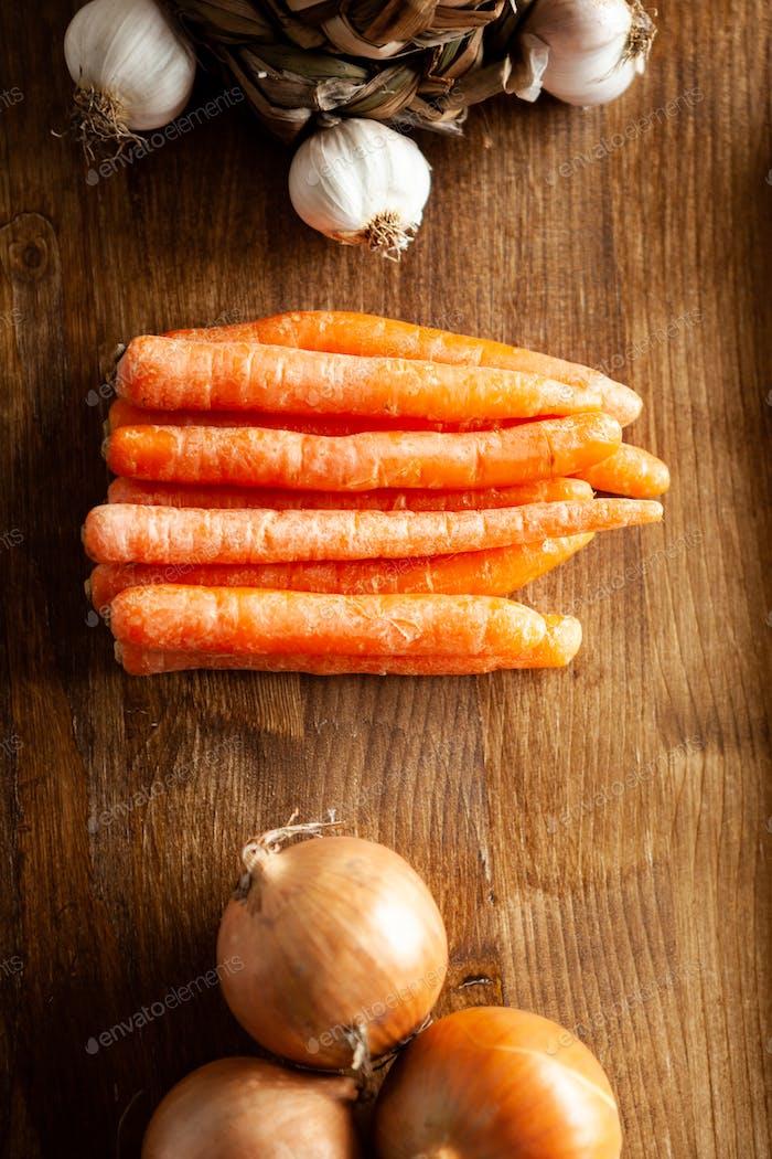 Draufsicht von frischen Karotten neben weißer Zwiebel und Knoblauch auf rustikalem Holztisch