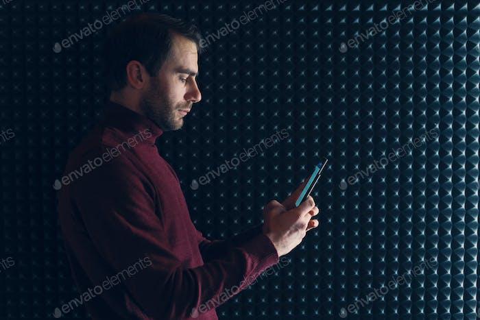 Улыбающийся уверенный человек держит смартфон на сером фоне