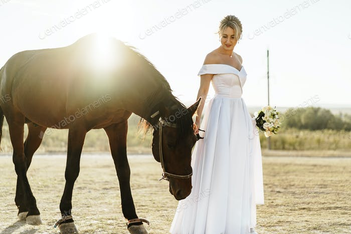 Portrait of a beautiful bride with horse