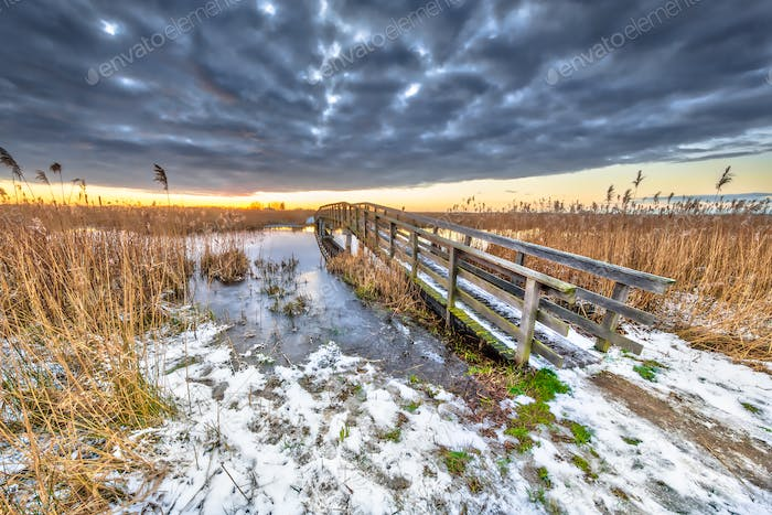 Wooden walking bridge in snowy Winter landscape