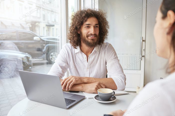 Cheerful young man with beard and brown curly hair meeting friend in coffee shop, working remotely