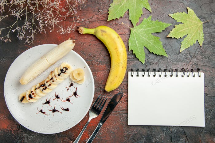 top view delicious banana with sliced pieces inside plate on the dark background fruit sweet photo