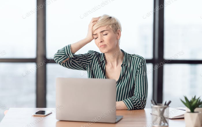 Lady Touching Head Suffering From Pain Sitting In Modern Office