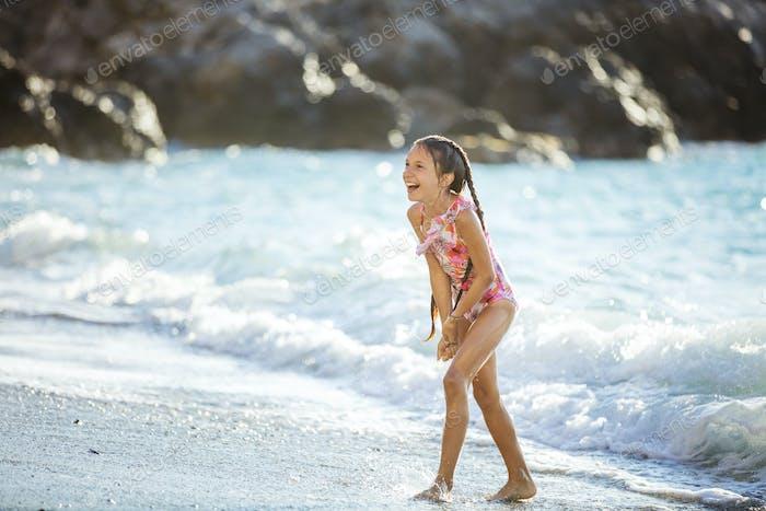 Chica feliz jugando en la playa