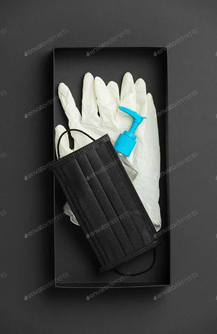 Protective face mask, sanitizer gel and lab gloves in black box on black paper background flat lay