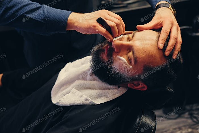 Barber shaving bearded male with a sharp razor.