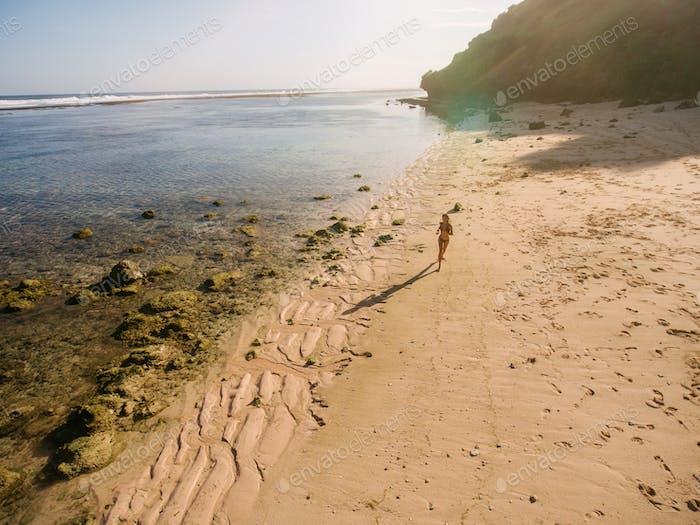Schöner tropischer Strand mit einer Frau läuft