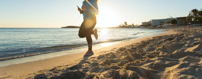 close up of young healthy lifestyle fitness woman running at sunrise beach