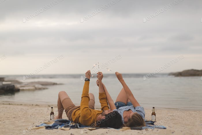Rear view of young Caucasian couple playing with fire cracker while lying at beach