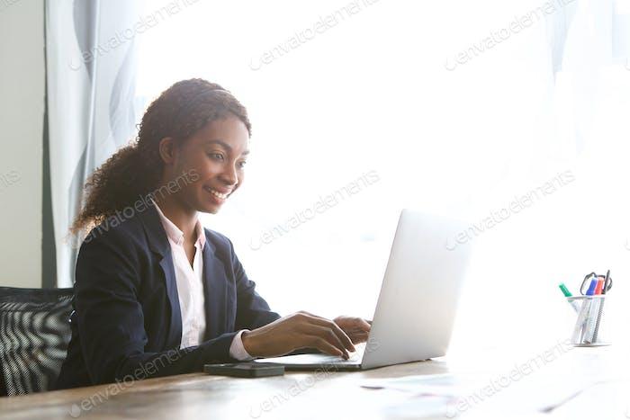 улыбающаяся молодая африканская американская бизнес-женщина работает ноутбук в офисе