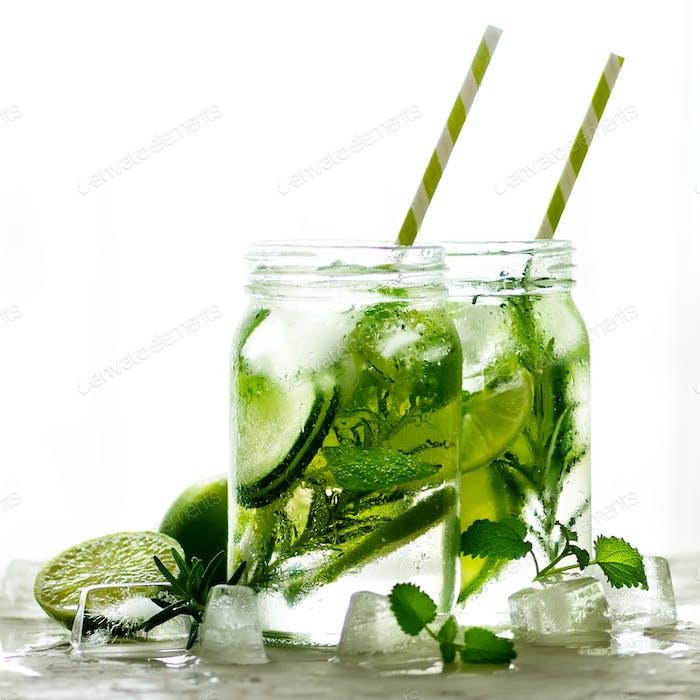 Холодная и освежающий детокс вода с лаймом, огурцом, розмарином и льдом в стеклянной банке. Копипространства