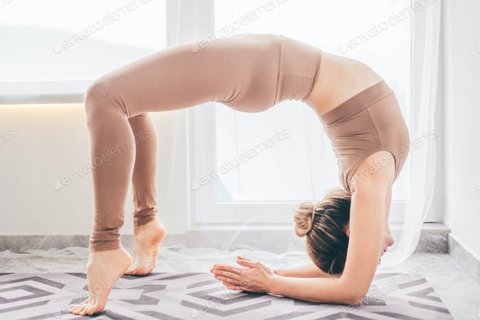 Schöne junge Frau in Sportbekleidung, die Yogaübungen macht.