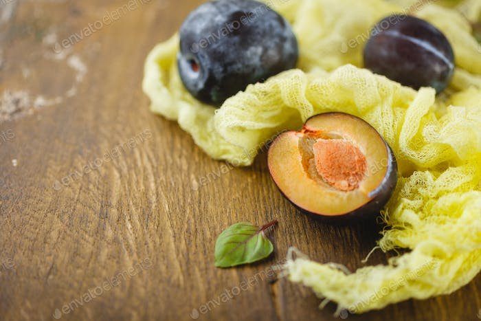 Plums on wooden background