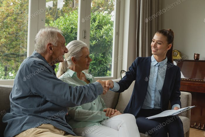 Side view of active senior Caucasian man shaking hands with real estate agent in living room at home
