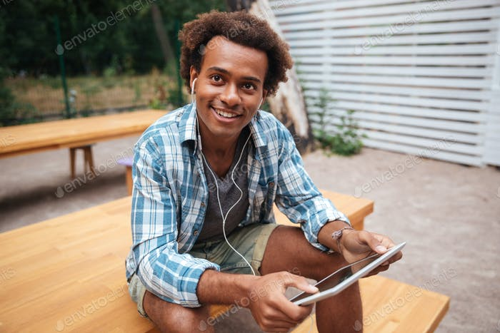 Happy african young man listening to music from tablet