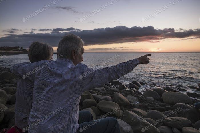 Романтическая деятельность для взрослых пожилых пар сидя на пляже, глядя на закат