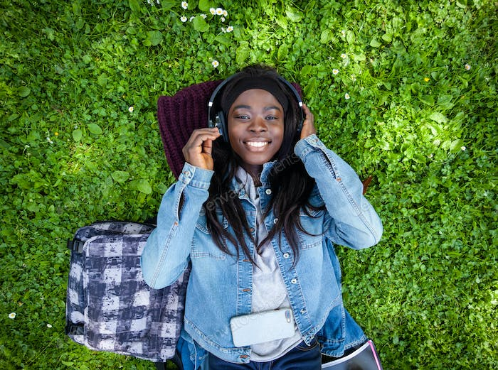 Top view of african woman listening to music with headphones.