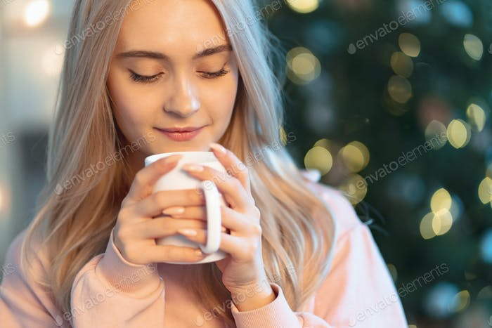 A pretty young woman making a wish while drinking a hot cup of milk waiting holidays at home